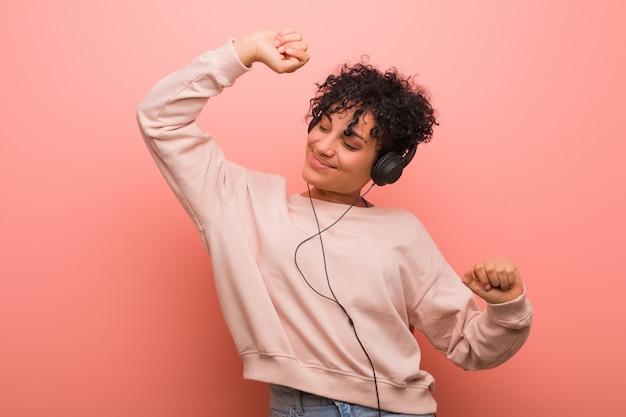 Jovem americana africano com uma marca de nascença, dançando e ouvindo música com um fone de ouvido