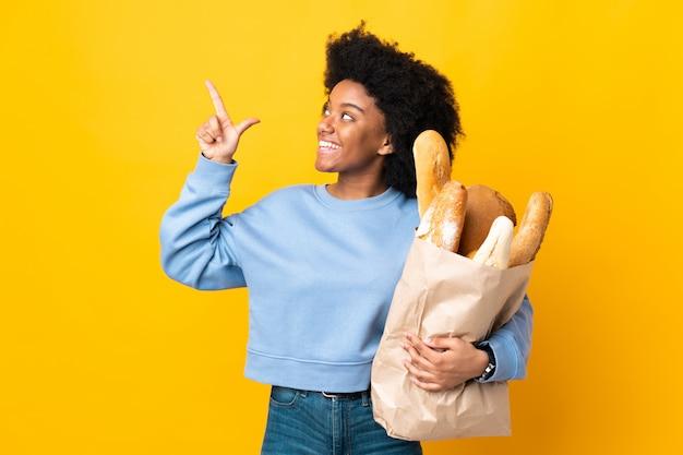 Jovem americana africano comprando algo pão isolado em fundo amarelo, apontando com o dedo indicador uma ótima idéia