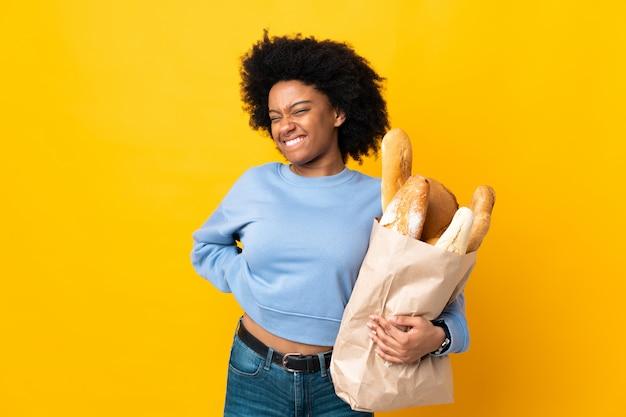 Jovem americana africano comprando algo pão isolado na parede amarela, sofrendo de dor nas costas por ter feito um esforço