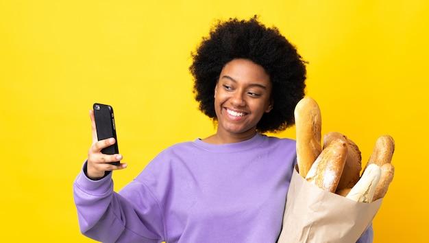 Jovem americana africano comprando algo pão na parede amarela, fazendo um selfie