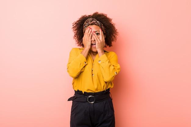 Jovem americana africano contra uma parede rosa piscar entre os dedos, assustada e nervosa.