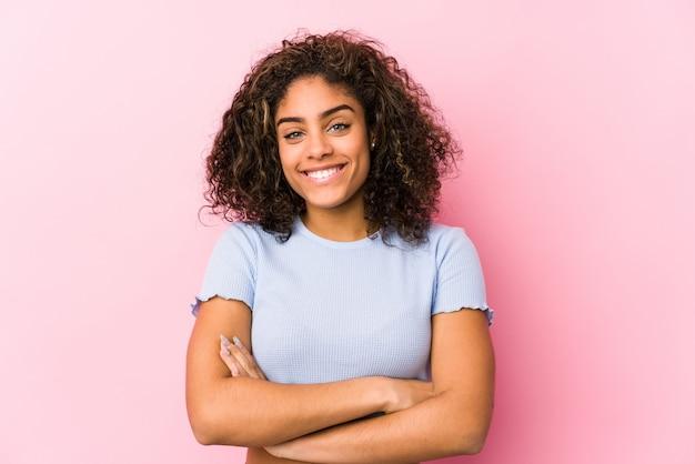 Jovem americana africano contra uma parede rosa que se sente confiante, cruzando os braços com determinação.