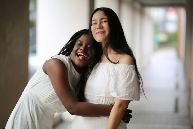 Jovem americana africano e mulher caucasiana em vestidos brancos