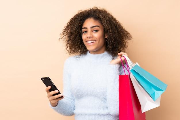Jovem americana africano isolada em bege segurando sacolas de compras e escrever uma mensagem com o celular para um amigo