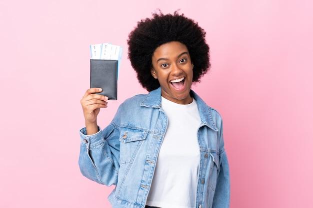 Jovem americana africano isolada em rosa feliz em férias com bilhetes de avião e passaporte