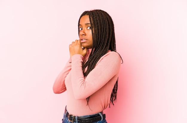 Jovem americana africano isolada em uma parede rosa assustada e com medo.