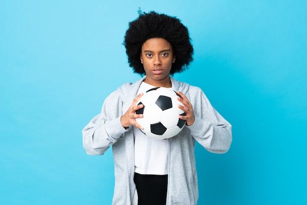 Jovem americana africano isolada na parede azul com bola de futebol