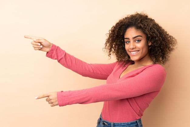 Jovem americana africano isolada na parede bege, apontando o dedo para o lado e apresentando um produto