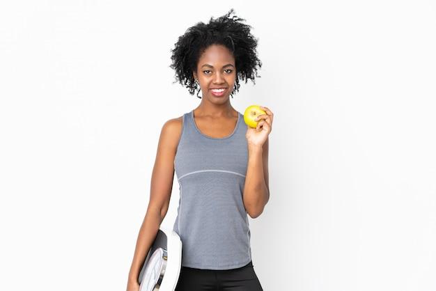 Jovem americana africano isolada na parede branca com máquina de pesagem e com uma maçã