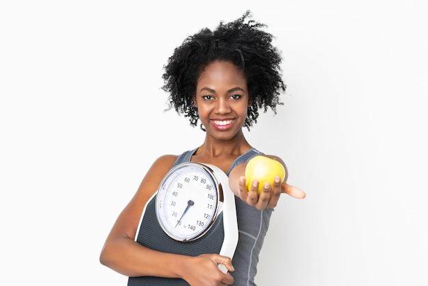 Jovem americana africano isolada na parede branca, segurando a máquina de pesagem e oferecendo uma maçã