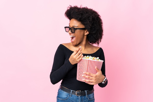 Jovem americana africano isolada na parede rosa com óculos 3d e segurando um grande balde de pipocas enquanto olha de lado