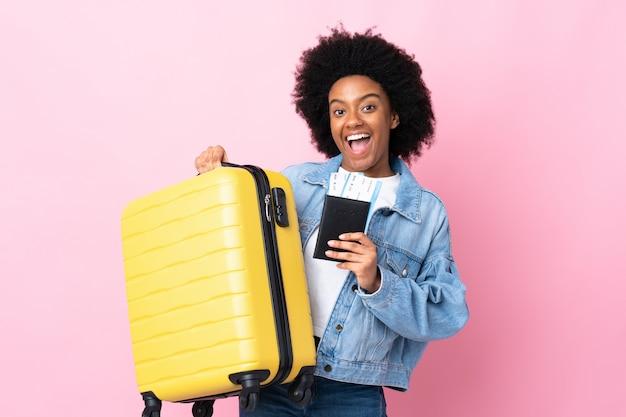 Jovem americana africano isolada na parede rosa em férias com mala e passaporte
