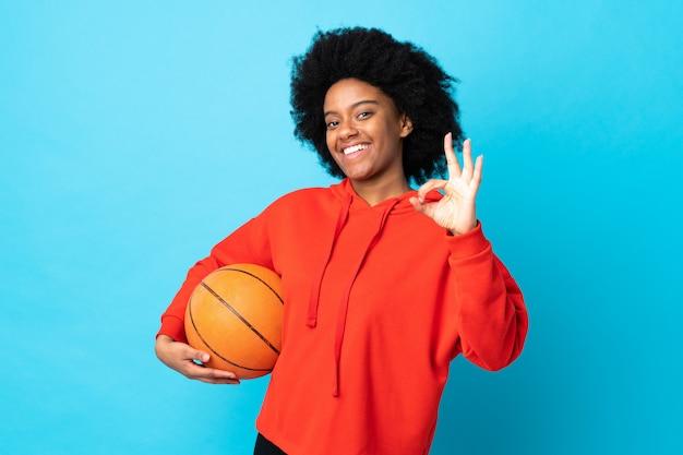 Jovem americana africano isolada no azul jogando basquete e fazendo sinal de ok