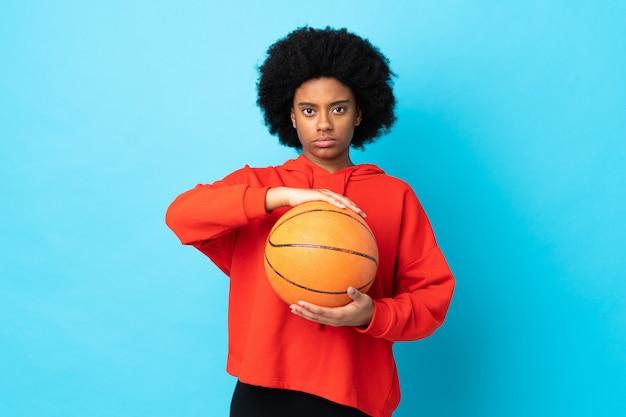 Jovem americana africano isolada no azul jogando basquete
