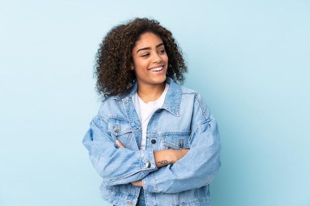 Jovem americana africano isolada no espaço azul feliz e sorridente
