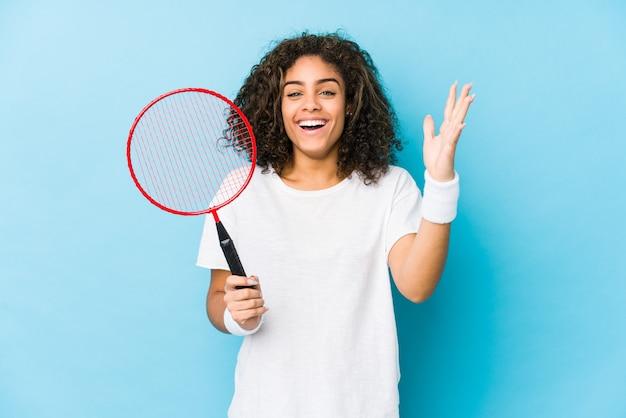 Jovem americana africano jogando badminton, recebendo uma surpresa agradável, animado e levantando as mãos.