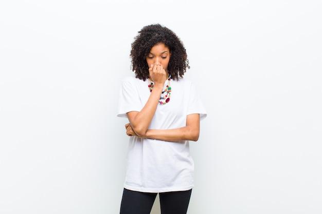 Jovem americana africano legal, sentindo-se sério, pensativo e preocupado, olhando de soslaio com a mão pressionada contra o queixo