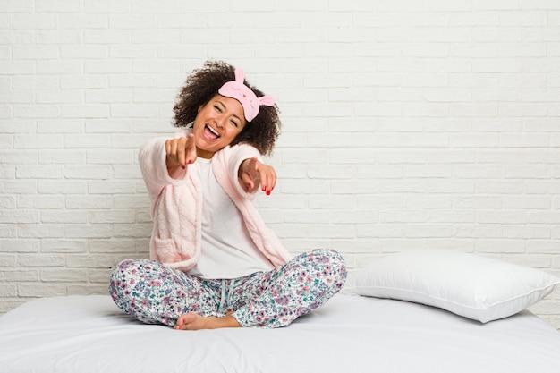 Jovem americana africano na cama vestindo pijama alegre sorrisos apontando para a frente.