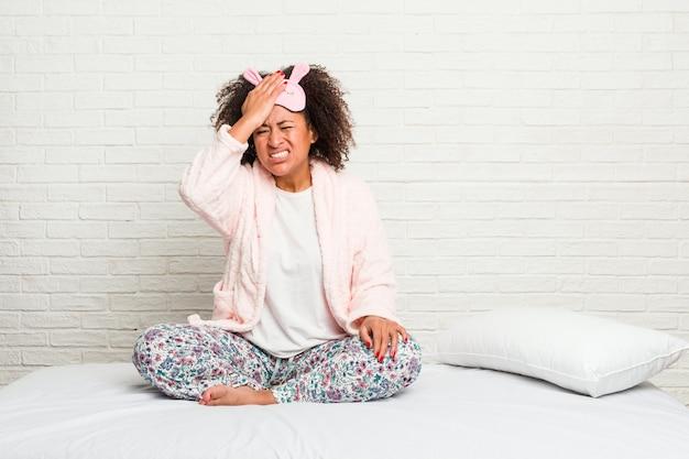 Jovem americana africano na cama vestindo pijama esquecendo algo, batendo na testa com a palma da mão e fechando os olhos.