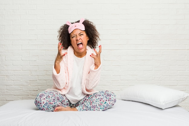 Jovem americana africano na cama vestindo pijama gritando de raiva.