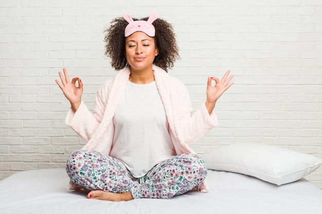 Jovem americana africano na cama vestindo pijama relaxa após um duro dia de trabalho, ela está realizando ioga.