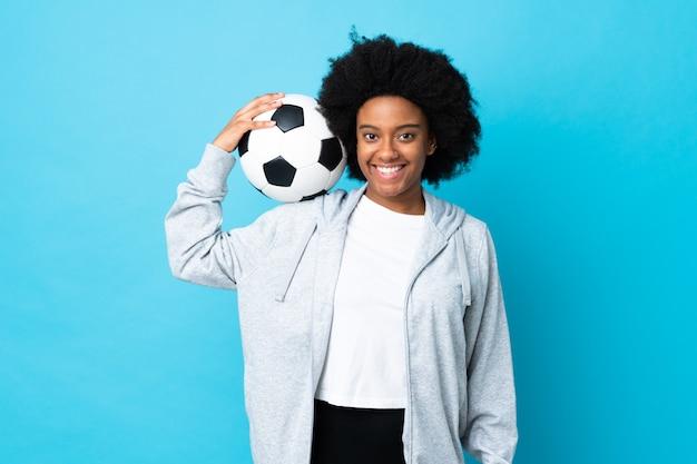 Jovem americana africano na parede azul com bola de futebol