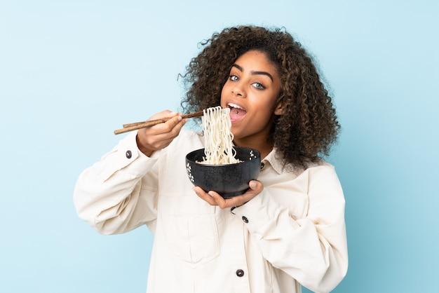 Jovem americana africano na parede azul, segurando uma tigela de macarrão com pauzinhos e comê-lo