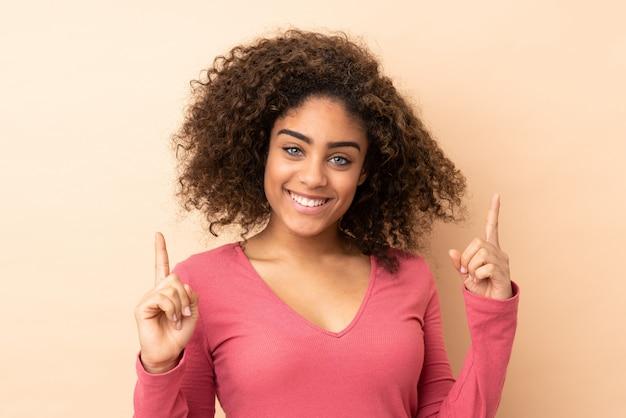 Jovem americana africano na parede bege apontando para cima uma ótima idéia