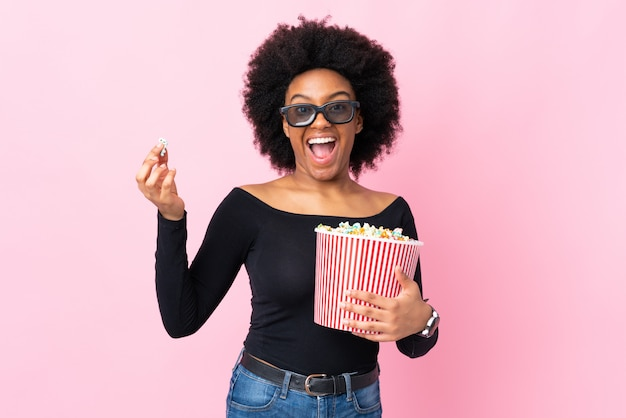Jovem americana africano na parede rosa com óculos 3d e segurando um grande balde de pipocas