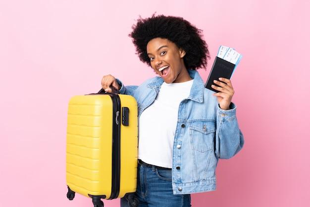 Jovem americana africano na parede rosa em férias com mala e passaporte