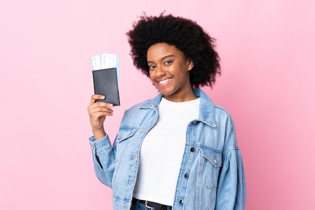 Jovem americana africano na parede rosa feliz em férias com bilhetes de avião e passaporte