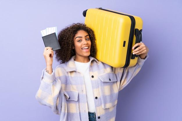 Jovem americana africano na parede roxa em férias com mala e passaporte