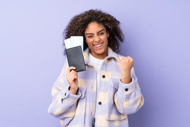 Jovem americana africano na parede roxa feliz com bilhetes de avião e passaporte