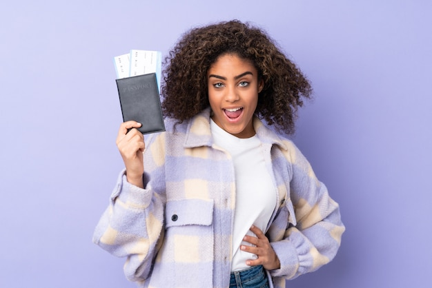 Jovem americana africano na parede roxa feliz em férias com bilhetes de avião e passaporte
