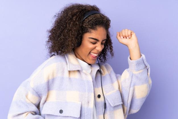 Jovem americana africano na parede roxa, ouvir música e dançar