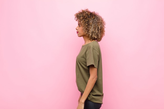 Jovem americana africano na vista de perfil, olhando para copiar o espaço à frente, pensando, imaginando ou sonhando acordado contra a parede rosa