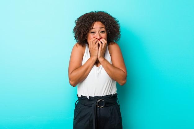 Jovem americana africano rindo de algo, cobrindo a boca com as mãos