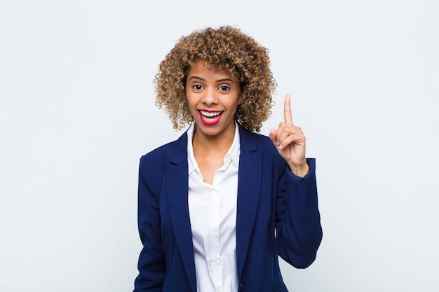 Jovem americana africano se sentindo como um gênio feliz e animado depois de perceber uma idéia, alegremente levantando o dedo, eureka! contra a parede