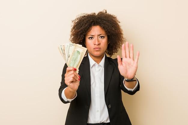 Jovem americana africano segurando dólares em pé com a mão estendida, mostrando o sinal de stop, impedindo-o.