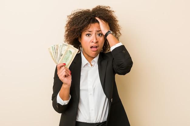 Jovem americana africano segurando dólares sendo chocado, ela se lembrou de importante reunião.