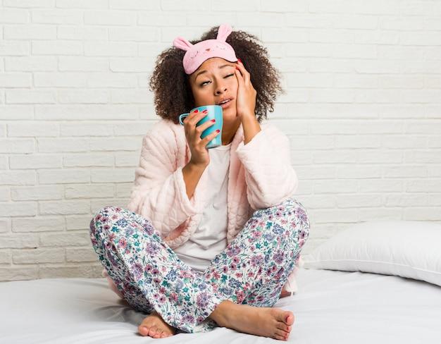 Jovem americana africano segurando um copo na cama
