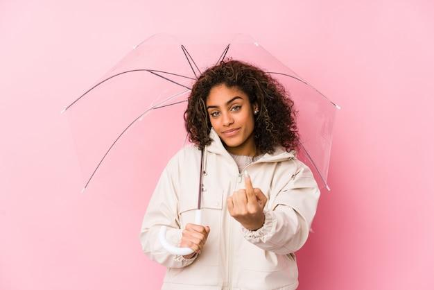 Jovem americana africano segurando um guarda-chuva apontando com o dedo para você, como se convidando se aproximar.