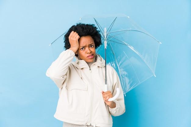 Jovem americana africano segurando um guarda-chuva isolado sendo chocado, ela se lembrou de uma reunião importante.