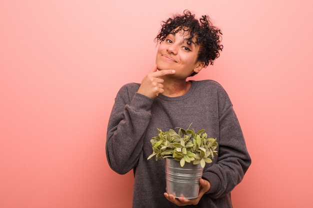 Jovem americana africano segurando uma planta lateralmente com expressão duvidosa e cética.