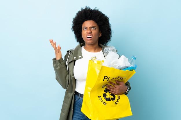 Jovem americana africano segurando uma sacola de reciclagem na parede colorida estressado oprimido