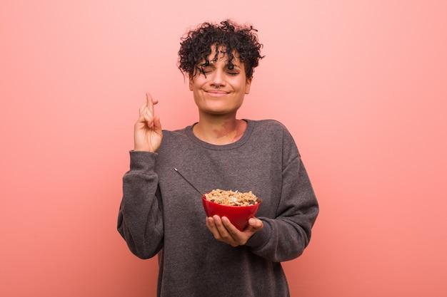 Jovem americana africano segurando uma tigela de cereais, cruzando os dedos por ter sorte