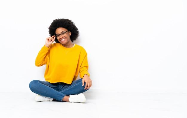 Jovem americana africano, sentada no chão com óculos e feliz