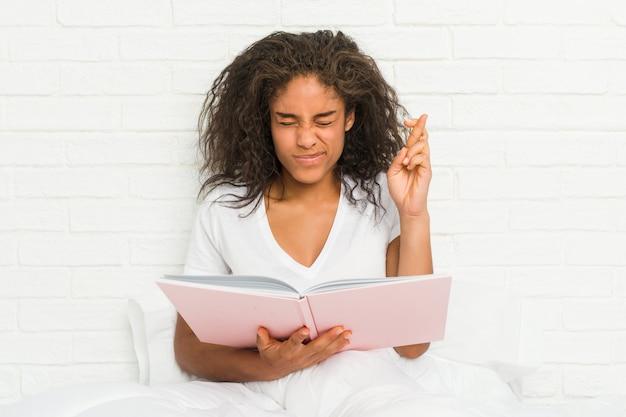 Jovem americana africano sentado na cama estudando cruzar os dedos por ter sorte