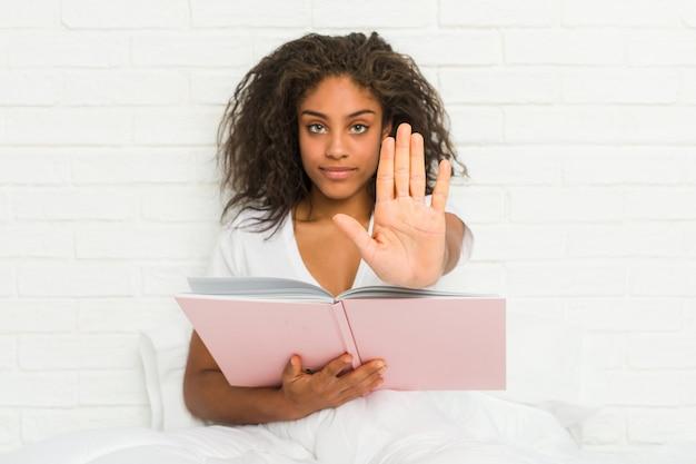 Jovem americana africano sentado na cama estudando em pé com a mão estendida, mostrando o sinal de stop, impedindo-o.