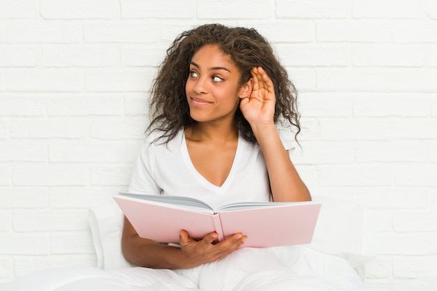 Jovem americana africano sentado na cama estudando tentando ouvir uma fofoca.
